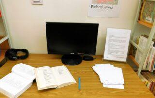 Stół z komputerem, książką i kartkami papieru